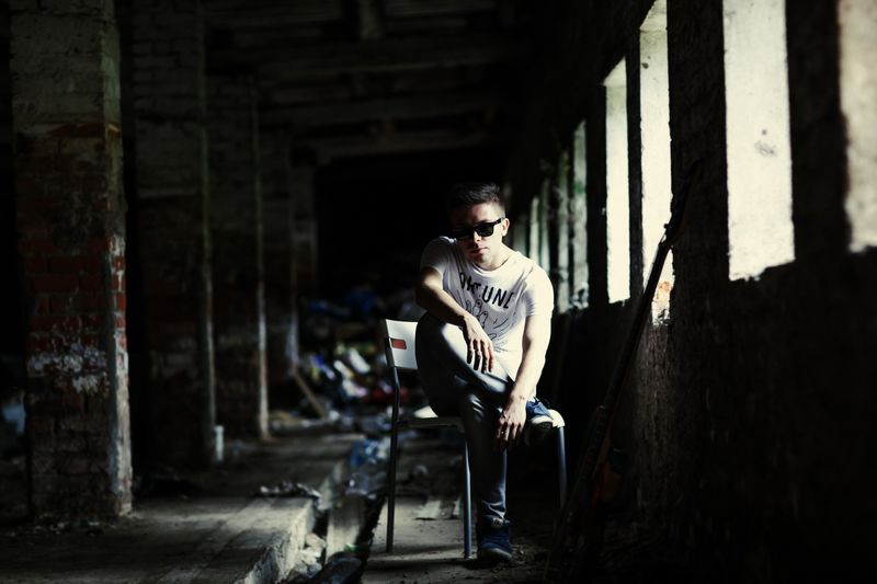 Man in sunglasses sitting in abandoned building