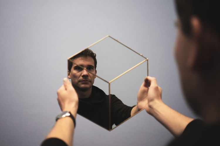 Man holding mirror with reflection against white wall