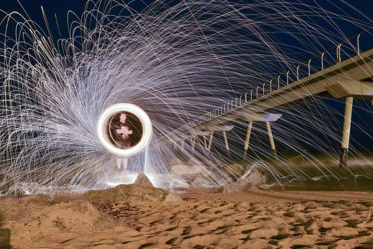 Man standing by wire wool at night