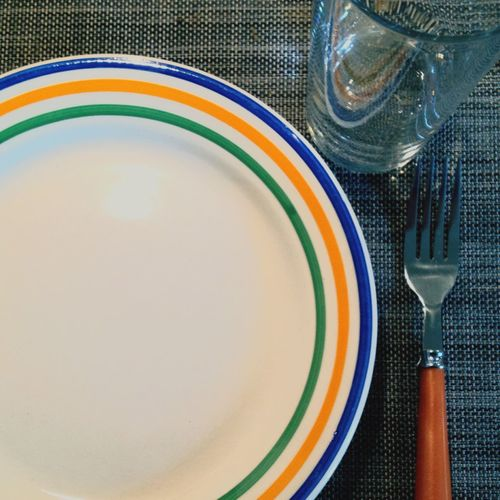 Directly above shot of multi colored plate with fork and drinking glass on table