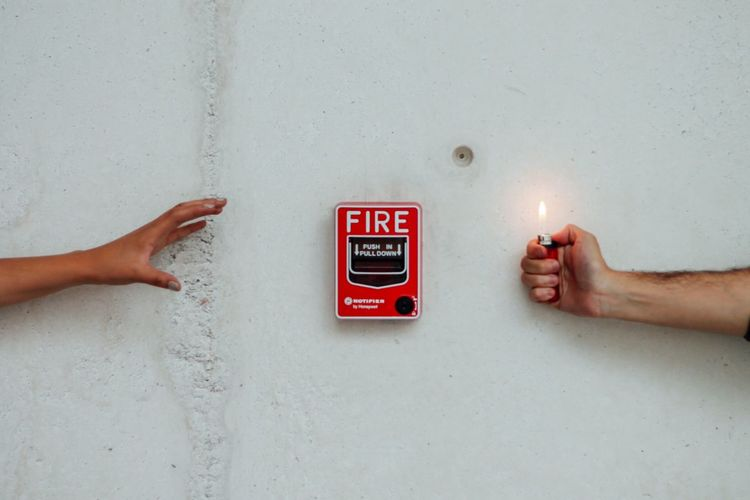 Cropped image of hand holding illuminated lighter against wall