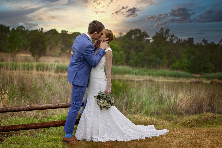 Rear view of couple kissing on land against sky