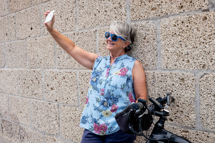 Smiling senior woman taking selfie while standing against wall