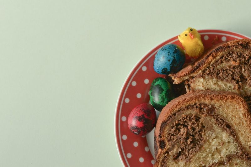 Directly above view of easter eggs and cake served in plate on white background