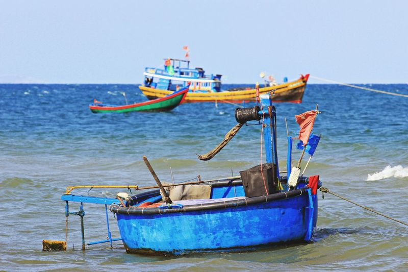 Fishing boats moored on sea against clear sky