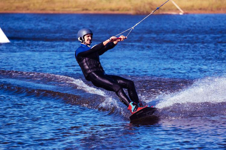 Young man kiteboarding on sea