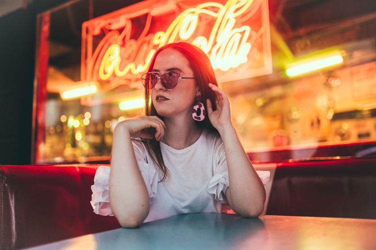 Portrait of young woman sitting on table at restaurant