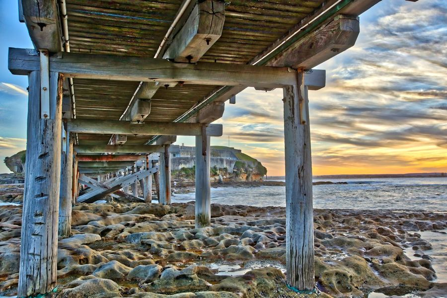 Under the wooden bridge at La Perouse. Extreme HDR, did awesome stuff to the wood grain HDR La Perouse Nature No People Outdoors Rocks Sea Sky Sunset Underneath Water Wood - Material