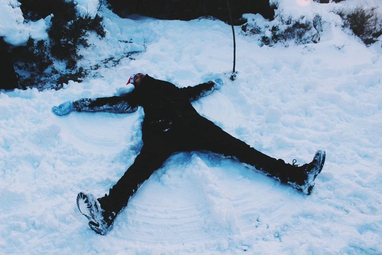 High Angle View Of Man Lying On Snow Covered Field