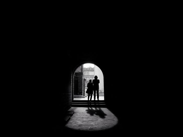 Rear View Of Silhouette People Standing At Archway