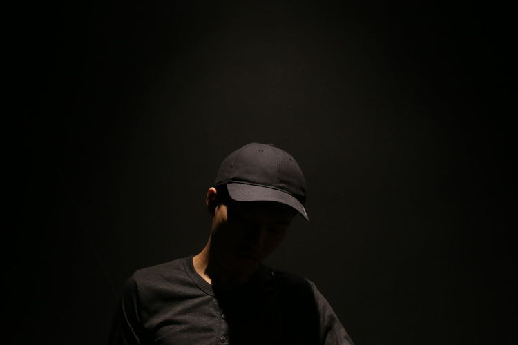 Man wearing cap standing against black background