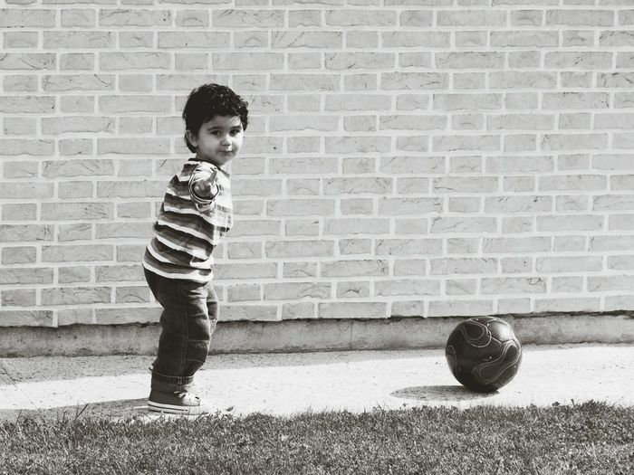 Side View Portrait Of Boy Gesturing While Standing By Soccer Ball