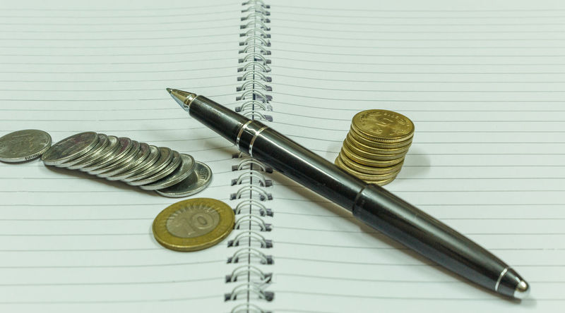 Image depicting blank spiral notebook with a black vintage pen placed over with India currency coins used for financial investments or calculation. With selective focus on the subject. Planning Calculator Calculator,white Close-up Day Education Finance Fountain Pen Gold Colored Indoors  Metal No People Note Pad Spiral Still Life