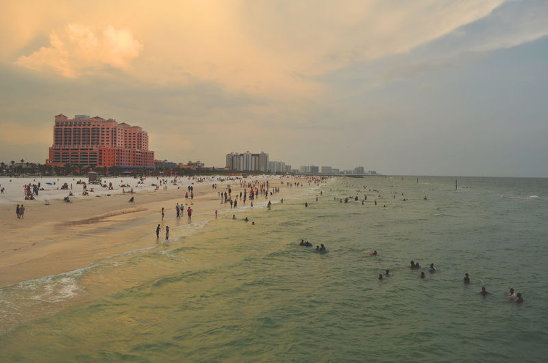 People enjoying at beach against sky during sunset