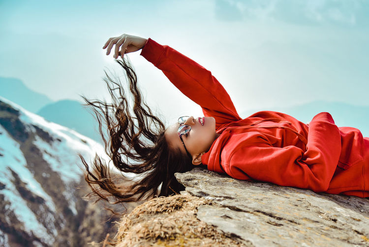 Woman tossing hair while lying on rock against sky