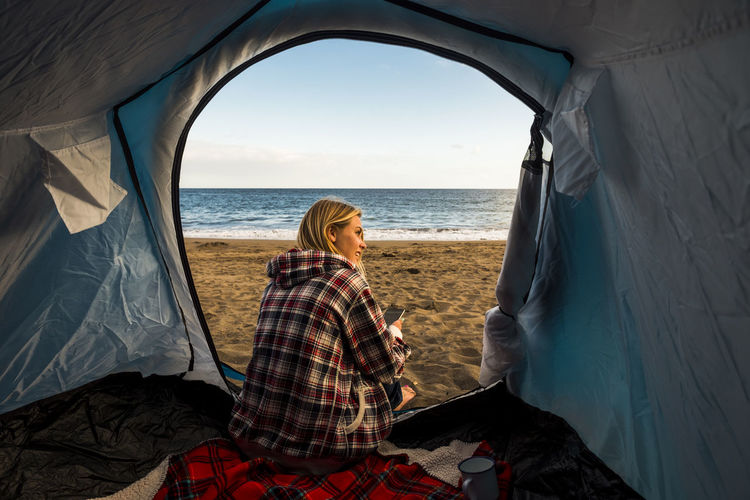 Woman sitting in tent at beach against sky