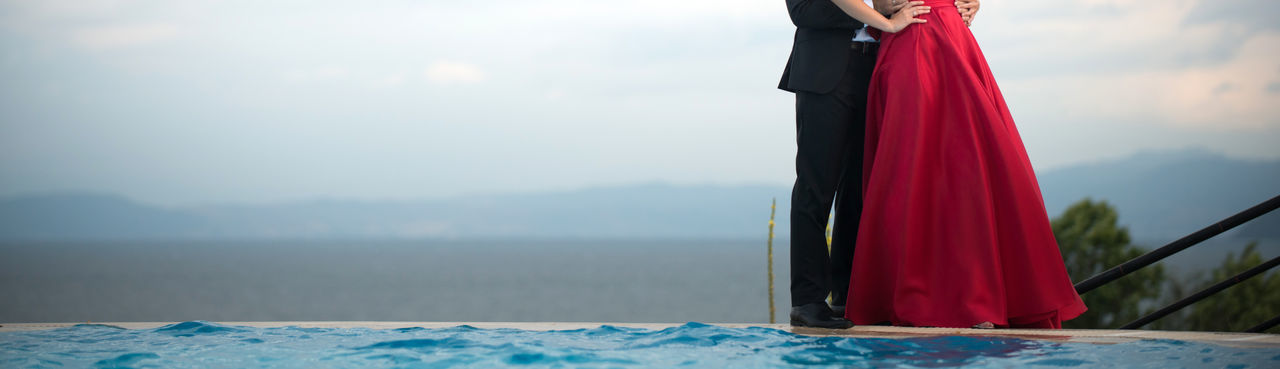 Low section of couple standing by infinity pool against sky