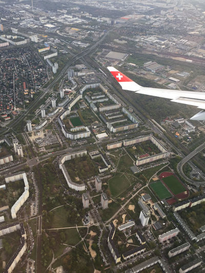 A wing of the Swiss airline Swiss, approaching Berlin, Germany. Berlin Plane Travelling Wing Aerial View Air Vehicle Airplane Architecture Building Building Exterior Built Structure City Cityscape Day High Angle View Mode Of Transportation Nature No People Outdoors Overpass Residential District Road Skyscraper Swiss Switzerland Transportation Travel Urban Living Urban Travel The Traveler - 2018 EyeEm Awards It's About The Journey