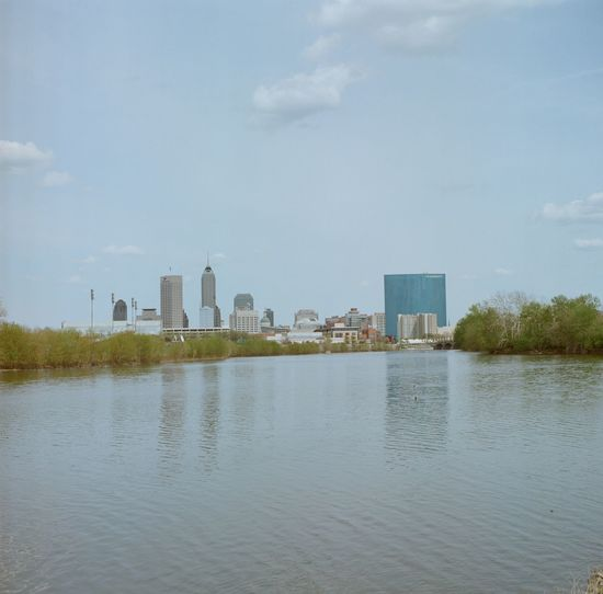 The White River with Indianapolis skyline and blue sky in Indianapolis, Indiana. Architecture Built Structure City Cityscape Cloud Cloud - Sky Day Film Photography Indiana Indianapolis  MidWest Modern No People Office Building Outdoors Rippled River Sky Skyscraper Summer Tall - High Tree Urban Skyline Water Waterfront