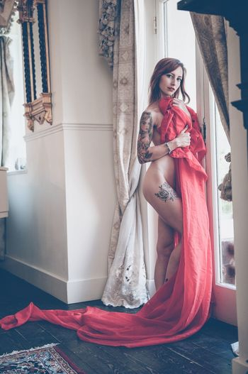 Portrait Of Naked Woman Holding Red Textile At Home