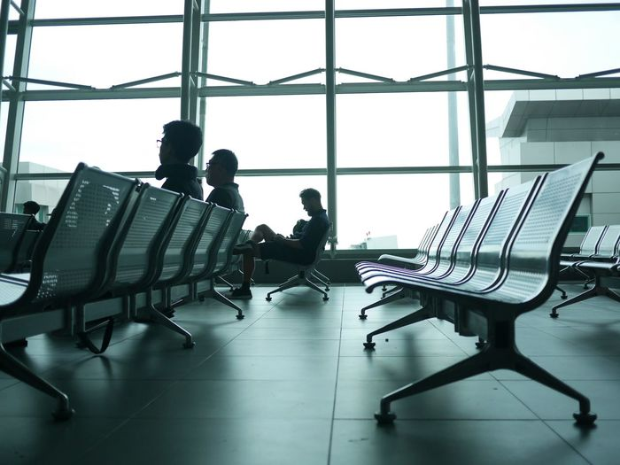 Men sitting on benches in waiting room at airport departure area