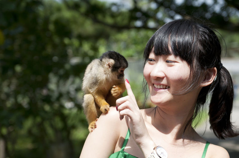 Portrait of woman playing with monkey