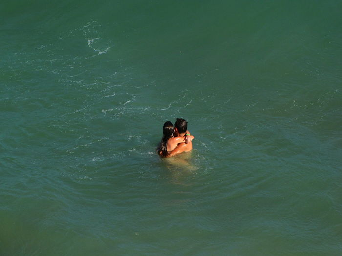 High angle view of romantic couple embracing in sea