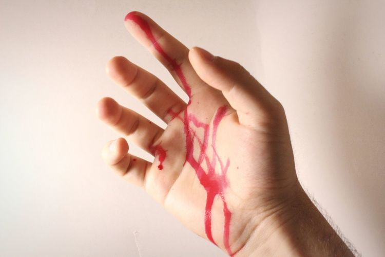 Cropped hand of man with blood against wall