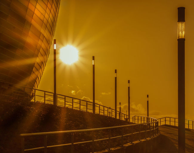 Illuminated street light against sky during sunset