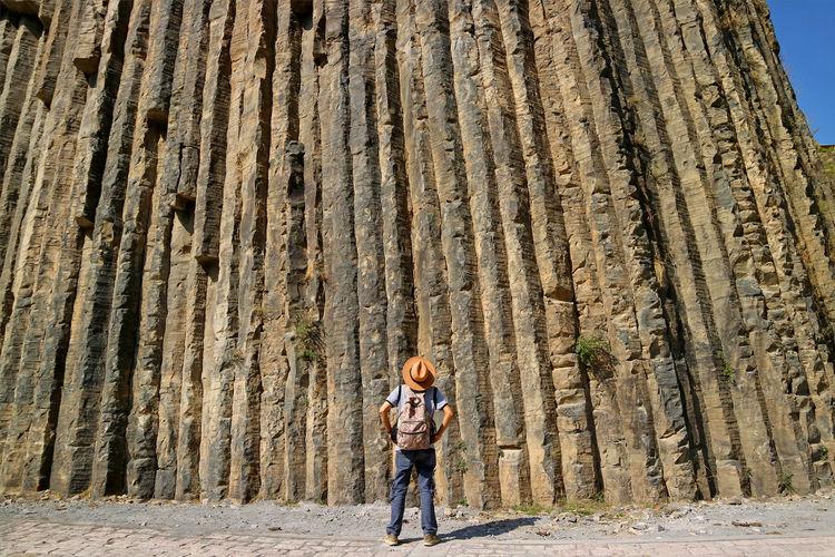 Traveler looking up to 50 meters high breathtaking basalt columns at garni gorge, armenia