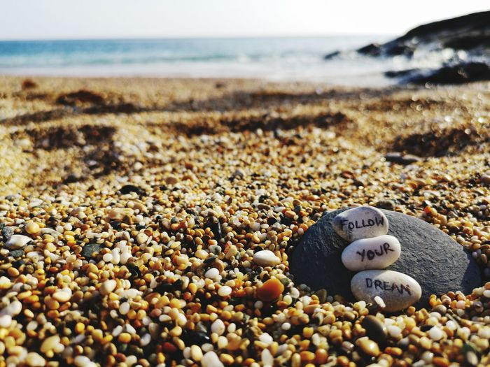 Close-up of pebbles with words on beach