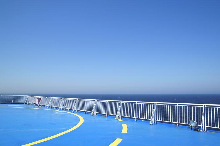 Helipad on ship against clear blue sky