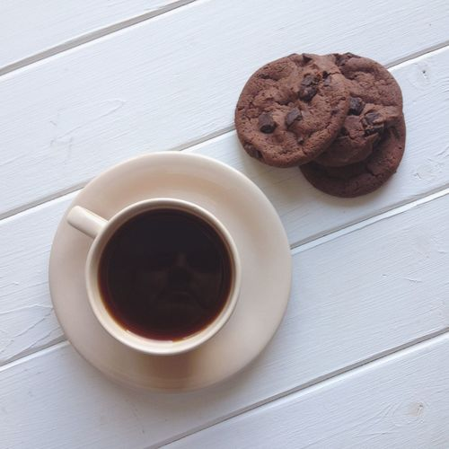 High Angle View Of Black Coffee With Cookies Served On Table