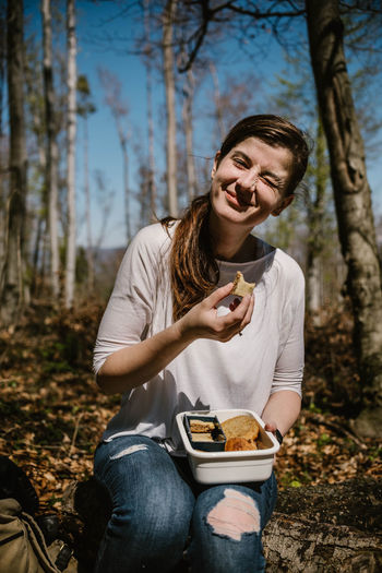 Portrait of woman winking while having food at forest