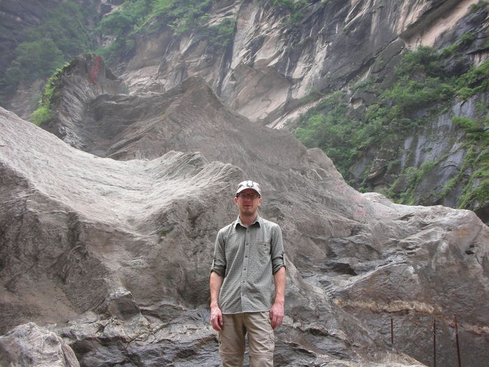 Portrait of man standing against rock formations