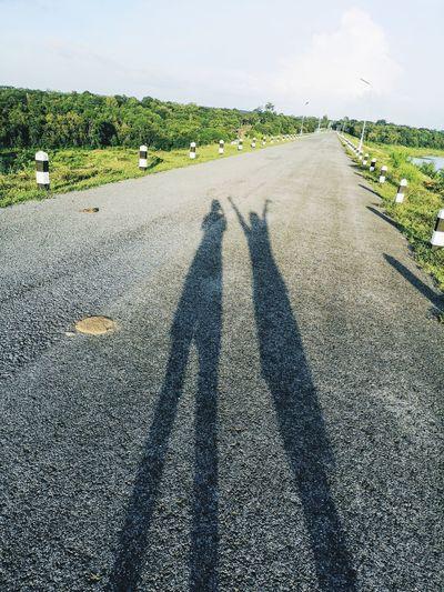 Shadow of man on road against sky