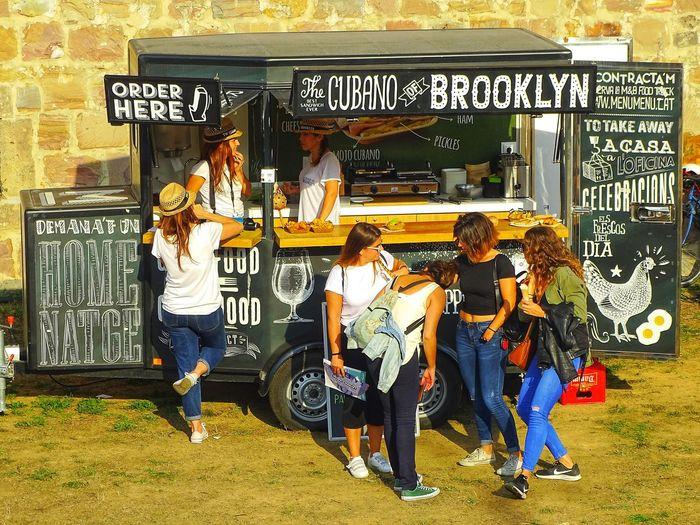 Happy female friends standing by food truck on field