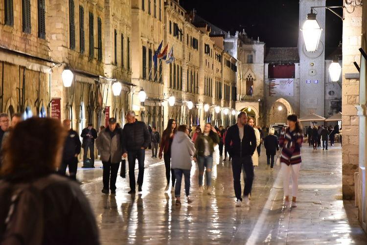 Crowd walking on illuminated city at night