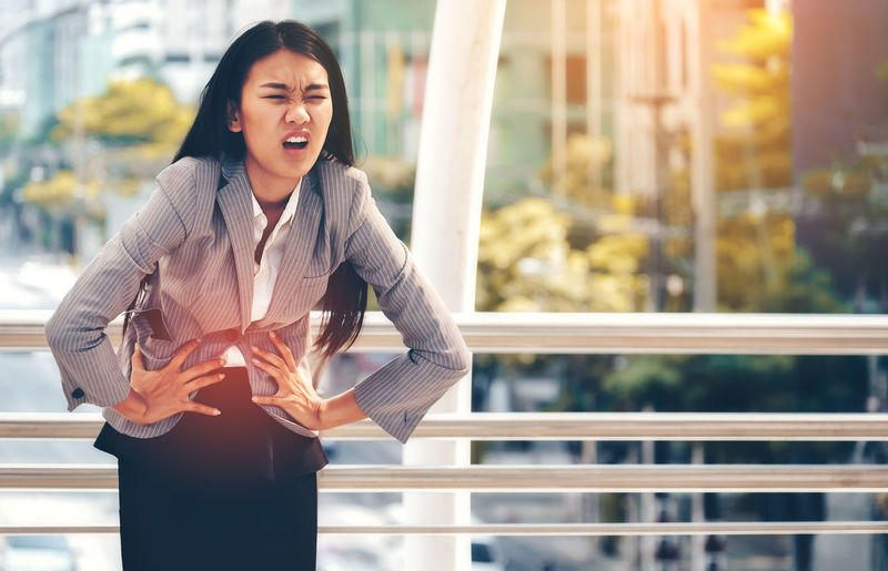 Businesswoman with stomachache standing against railing