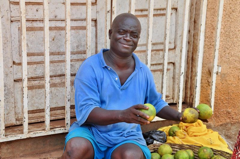 Portrait Of Smiling Male Vendor Sitting With Fruits Against Gate
