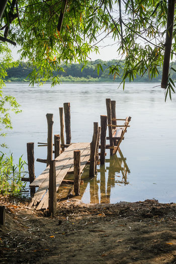 Wooden posts on beach by lake