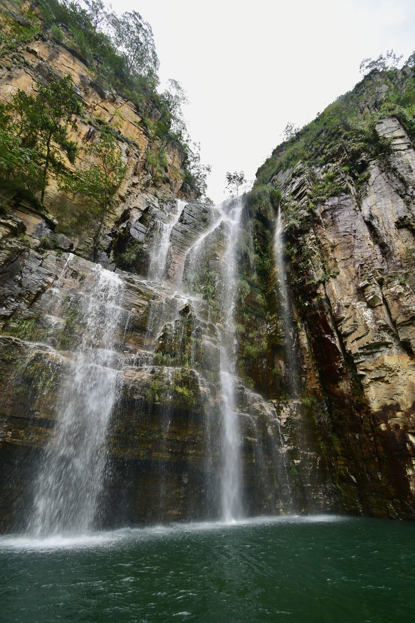 LOW ANGLE VIEW OF WATERFALL AGAINST ROCKS