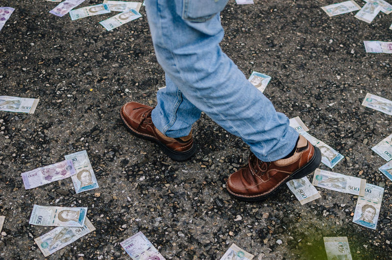 Low section of person walking by paper currency on street