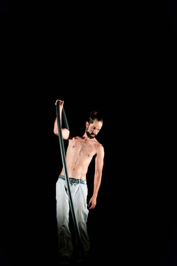 Circus Adult Arms Raised Black Background Copy Space Cut Out Front View Holding Human Arm Human Limb Indoors  Lifestyles Men Muscular Build One Person Shirtless Skill  Standing Studio Shot Three Quarter Length Young Adult Young Men