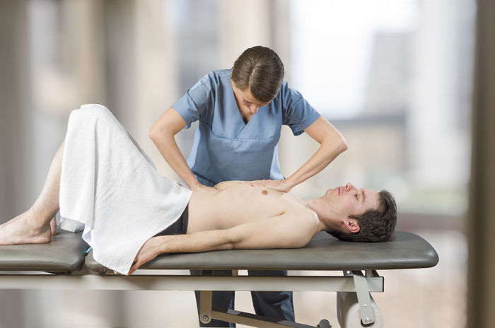Physiotherapist, chiropractor is doing a liver visceral fascia. Massage to a man patient. Osteopathy Back Doctor  Man Medicine Pain Therapy Woman Cervical Chiropractor Clinic Healthcare And Medicine Injury Manipulation Massage Medical Muscles Muscular Patient person Physiotherapy Professional Stretching Therapist