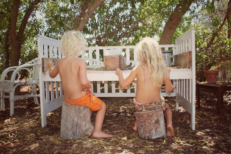 Rear view of shirtless children playing while sitting on tree stumps in yard