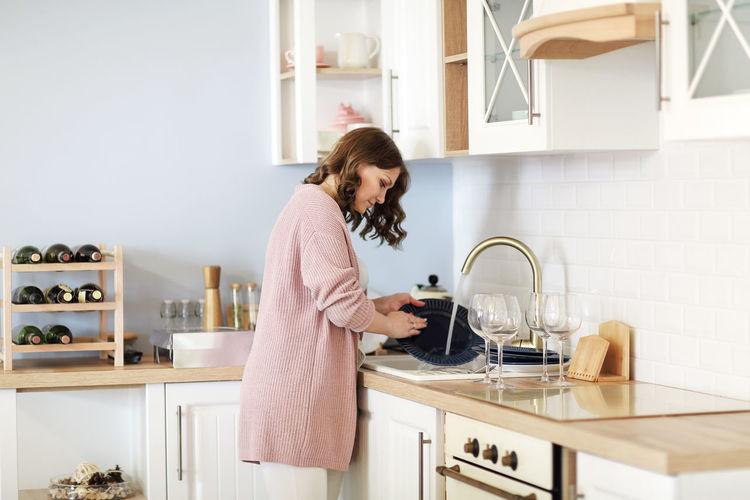 Woman walking dish in kitchen