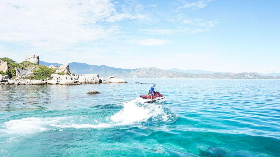 Man jet boating in sea against sky