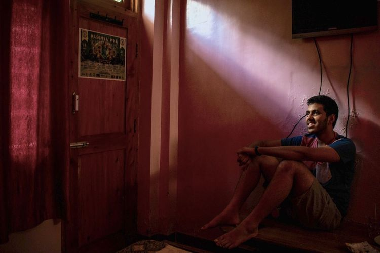 Young man looking away while sitting in house