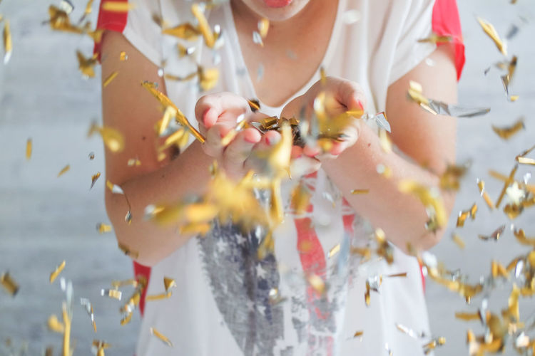 Close-Up Of Hand Holding Golden Confetti